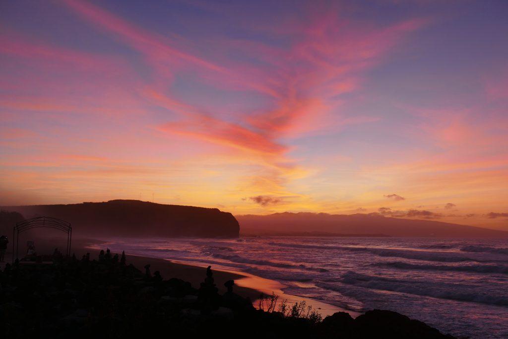 Geniet (van een zonsondergang) op het strand